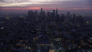 AX0156_043 - 8K stock footage aerial video tilting from MacArthur Park to reveal Downtown Los Angeles skyline at sunrise, California