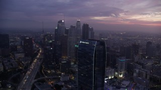 AX0156_050 - 8K stock footage aerial video of a reverse view of the Wilshire Grand Center in Downtown Los Angeles at sunrise, California, reveal the Ritz-Carlton