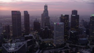 AX0156_055 - 8K stock footage aerial video of towering skyscrapers around the Westin Bonaventure Hotel in Downtown Los Angeles at sunrise, California