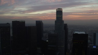 AX0156_075 - 8K stock footage aerial video flying between skyscrapers in Downtown Los Angeles, California, revealing City Hall early in the morning