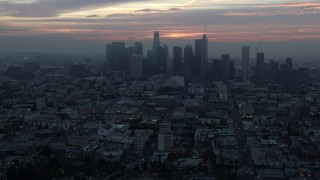AX0156_084 - 8K stock footage aerial video flying over MacArthur Park to approach the Downtown Los Angeles, California skyline on a hazy morning