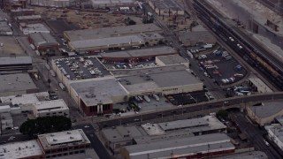 AX0156_101 - 8K stock footage aerial video of warehouse building by the Fourth Street Viaduct in Boyle Heights, Los Angeles, California at sunrise