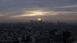 AX0156_110 - 8K stock footage aerial video flying over Koreatown office buildings to approach the skyline of Downtown Los Angeles, California at sunrise