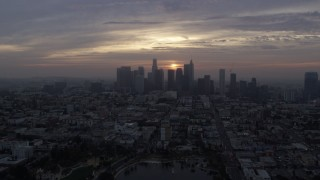 AX0156_111 - 8K stock footage aerial video approaching the skyline of Downtown Los Angeles, California at sunrise, fly over MacArthur Park