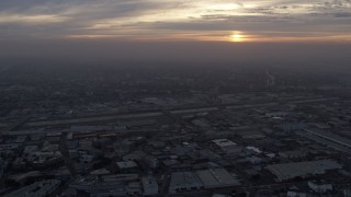 AX0156_114 - 8K stock footage aerial video flying over downtown warehouse buildings to approach the LA River and Boyle Heights in Los Angeles, California at sunrise