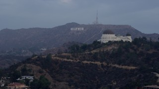 AX0156_118 - 8K stock footage aerial video of a view of the Hollywood Sign seen while passing Griffith Observatory at sunrise in Los Angeles, California