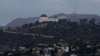 AX0156_120 - 8K stock footage aerial video flying by Griffith Observatory to reveal the Hollywood Sign at sunrise, Los Angeles, California