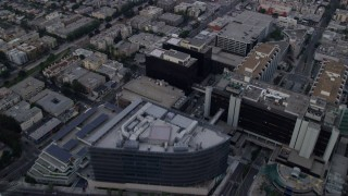 AX0156_121 - 8K stock footage aerial video flying over mansions to approach Beverly Center and Cedars-Sinai Medical Center at sunrise in Beverly Hills, California