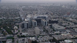 AX0156_126 - 8K stock footage aerial video orbiting Cedars-Sinai Medical Center and Beverly Center, sunrise, Beverly Hills, California