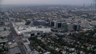 AX0156_128 - 8K stock footage aerial video orbiting Beverly Center adjacent to Cedars-Sinai Hospital and skyline in distance, sunrise, Beverly Hills, California