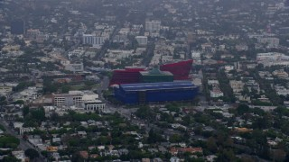 AX0156_129 - 8K stock footage aerial video of a side view of the MOCA Pacific Design Center, sunrise, Beverly Hills, California