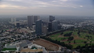 AX0156_131 - 8K stock footage aerial video orbiting office buildings and skyscrapers toward golf course, sunrise, Century City, California