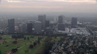 AX0156_132 - 8K stock footage aerial video flying over golf course along office buildings and skyscrapers, sunrise, Century City, California