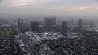 AX0156_133 - 8K stock footage aerial video passing by a shopping mall set against office buildings, sunrise, Century City, California