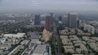 AX0156_135 - 8K stock footage aerial video orbiting away from Fox Tower and skyscrapers over Avenue of the Stars, sunrise, Century City, California