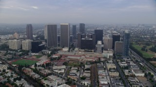 AX0156_137 - 8K stock footage aerial video orbiting away from skyscrapers and Beverly Hills High School, sunrise, Century City, California