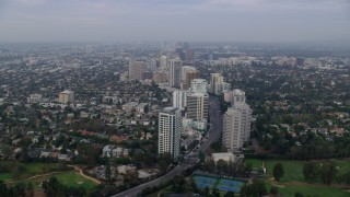 AX0156_138 - 8K stock footage aerial video following Wilshire Blvd over Los Angeles Country Club and The Windmill Links, sunrise, Century City, Beverly Hills, California
