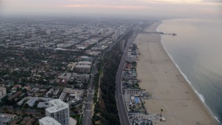 AX0156_146 - 8K stock footage aerial video flying over beach with Santa Monica Pier in the distance, sunrise, Santa Monica, California