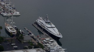 AX0156_176 - 8K stock footage aerial video of a mega yacht docked in harbor with helicopter on back, sunrise, Marina Del Rey, California