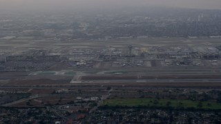 AX0156_180 - 8K stock footage aerial video tracking an airplane landing at LAX amongst thick cloud coverage, sunrise, Los Angeles, California