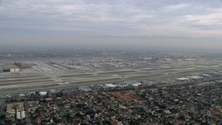 AX0156_189 - 8K stock footage aerial video of a sideview of LAX on a cloudy morning, sunrise, Los Angeles, California
