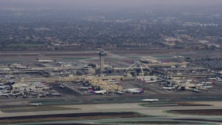 AX0156_190 - 8K stock footage aerial video of LAX and its control tower on a cloudy morning, sunrise, Los Angeles, California