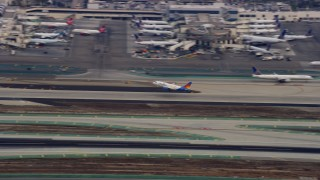 AX0156_191 - 8K stock footage aerial video tracking a jet taking off from LAX in the morning, California