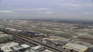 AX0156_193 - 8K stock footage aerial video tracking a FedEx jet taking off from LAX, California in the morning