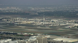 AX0157_004 - 8K stock footage aerial video tracking a plane taking off from LAX, cloudy, Los Angeles, California