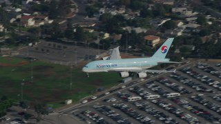 AX0157_006 - 8K stock footage aerial video tracking Korean Air A380 landing at LAX, cloudy, Los Angeles, California