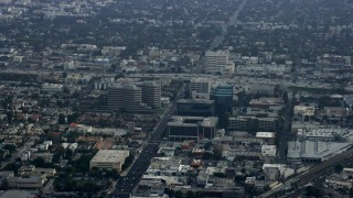 AX0157_012 - 8K stock footage aerial video passing by office buildings and freeways, haze, Santa Monica, California