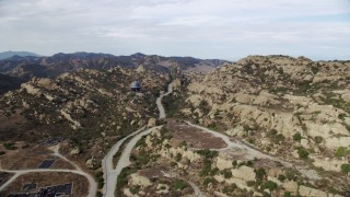 AX0157_040 - 8K stock footage aerial video flying over road leading to Aerojet Rocektdyne testing facility,  Brandeis, CA