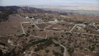 AX0157_047 - 8K stock footage aerial video approaching roads and buildings of the Rocektdyne aerospace testing facility, Brandeis, California