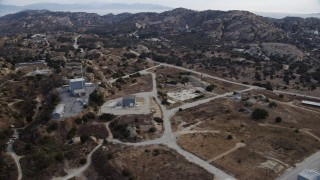 AX0157_050 - 8K stock footage aerial video flying over buildings at the Rocektdyne aerospace testing facility in Brandeis, CA