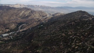 AX0157_053 - 8K stock footage aerial video flying over Simi Valley hills towards San Fernando Valley, California