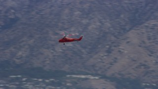 AX0157_086 - 8K stock footage aerial video tracking a Sikorsky S58T flying by mountains in Pacoima, California