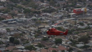 AX0157_087 - 8K stock footage aerial video tracking a Sikorsky S58T flying over Pacoima, California