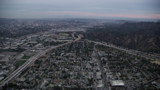 AX0158_003 - 8K stock footage aerial video flying towards the I-5 & 134 interchange at twilight, Glendale, California