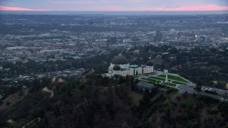 AX0158_014 - 8K stock footage aerial video orbiting Griffith Observatory from behind to reveal skyline and city sprawl, twilight, Los Angeles, California