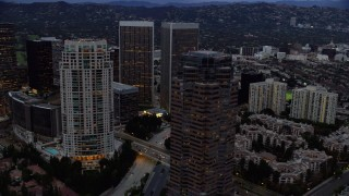 AX0158_035 - 8K stock footage aerial video orbiting office buildings and skyscrapers at twilight, Century City, California
