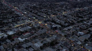 AX0158_037 - 8K stock footage aerial video flying over businesses and neighborhoods along La Cienega Boulevard and West Pico Blvd, twilight, Central Los Angeles, California