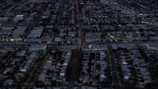 AX0158_038 - 8K stock footage aerial video following Pico Boulevard east over urban neighborhoods and businesses, twilight, Central Los Angeles, California