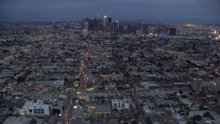 AX0158_043 - 8K stock footage aerial video of Downtown Los Angeles skyline from urban neighborhoods, California, twilight