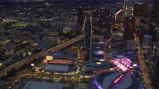 AX0158_061 - 8K stock footage aerial video flying by Staples Center, skyscrapers, and heavy 110 traffic at twilight, Downtown Los Angeles, California