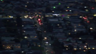 AX0158_062 - 8K stock footage aerial video of an LAPD helicopter flying over the city and streets at twilight in Los Angeles, California
