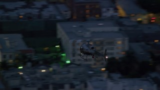 AX0158_063 - 8K stock footage aerial video of an LAPD helicopter flying over city buildings at twilight in Los Angeles, California