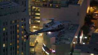 AX0158_064 - 8K stock footage aerial video of an LAPD helicopter flying over Los Angeles, California at twilight