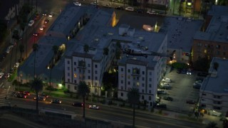 AX0158_067 - 8K stock footage aerial video tracking an LAPD helicopter over apartments and city streets at twilight in Los Angeles, California