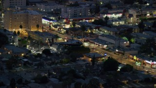 AX0158_069 - 8K stock footage aerial video tracking an LAPD helicopter flying over Hollywood, California at twilight