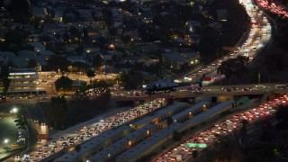AX0158_070 - 8K stock footage aerial video tracking LAPD helicopter over heavy freeway traffic at twilight in Hollywood, California